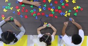 L'insegnante lascia insieme il giocattolo dell'alfabeto della corda dello studente stock footage