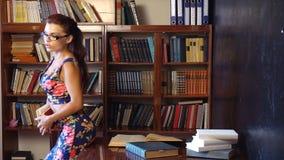 L'insegnante legge un libro nella biblioteca dell'università 1 archivi video