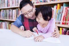 L'insegnante maschio aiuta una bambina a scrivere Fotografia Stock Libera da Diritti