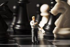 L'insegnante miniatura spiega le regole del gioco di scacchi a bordo Concetto di analisi di strategia di scacchi fotografie stock