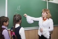 L'insegnante nell'aula con le scolare Immagine Stock