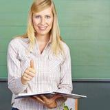 L'insegnante nella tenuta della scuola sfoglia su Fotografie Stock