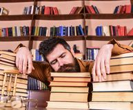 L'insegnante o lo studente con la barba cade addormentato sui libri, defocused Concetto di Overstudied Uomo sul fronte di sonno p Fotografia Stock