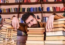 L'insegnante o lo studente con la barba cade addormentato sui libri, defocused L'uomo sul fronte di sonno pone fra i mucchi dei l Immagine Stock