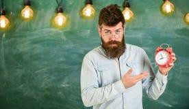 L'insegnante in occhiali tiene la sveglia Concetto di disciplina L'uomo con la barba ed i baffi sul fronte rigoroso stanno dentro fotografia stock libera da diritti