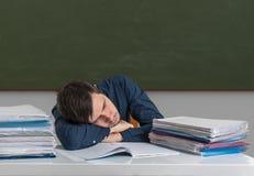 L'insegnante sovraccarico stanco sta dormendo sullo scrittorio in aula Immagine Stock Libera da Diritti