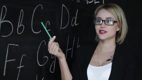 L'insegnante sta scrivendo la lettera dell'alfabeto sulla lavagna con gesso Istruzione nel concetto della scuola elementare stock footage
