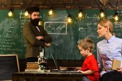 L'insegnante sta sedendosi alla tavola in aula, in professore e nello studente all'aula in una scuola, insegnante grazioso della  Immagine Stock Libera da Diritti
