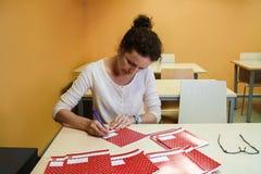L'insegnante sta sedendosi allo scrittorio e sta controllando i taccuini della scuola Fotografia Stock Libera da Diritti