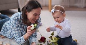 L'insertion de bébé et de mère a monté des fleurs dans le vase banque de vidéos