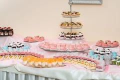 L'insieme dei dolci e dei dessert differenti dei dolci ha sistemato su un piatto Barra di caramella del partito Fotografie Stock Libere da Diritti