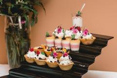 L'insieme dei dolci e dei dessert differenti dei dolci ha sistemato su un piatto Barra di caramella del partito Fotografie Stock