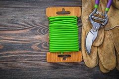 L'insieme dei guanti protettivi delle cesoie fa il giardinaggio cavo del legame sul boa di legno Immagine Stock Libera da Diritti