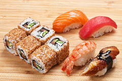 L'insieme dei sushi con i rotoli e il nigiri sono servito su un bordo di legno Fotografie Stock Libere da Diritti