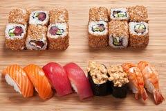 L'insieme dei sushi con i rotoli e il nigiri sono servito su un bordo di legno, sushi con il gamberetto del tonno, del salmone e  Fotografie Stock