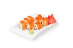 L'insieme dei sushi con il maki è servito in un bianco ceramico immagini stock