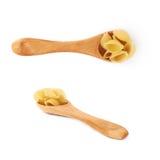 L'insieme del cucchiaio di legno ha riempito di pasta asciutta del conchiglie sopra fondo bianco isolato Fotografia Stock