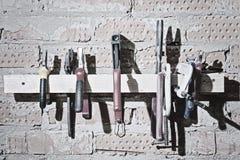 L'insieme del maschio differente foggia la vista sul muro di mattoni del garage, officina Pinze, taglierine, un vice, forbici, cu Fotografia Stock