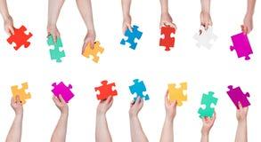 L'insieme del puzzle di colore collega in mani della gente Immagini Stock