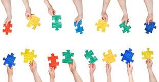 L'insieme del puzzle dipinto collega in mani della gente Fotografia Stock