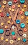 L'insieme della nonna Vecchie forbici e uno scattering dei bottoni colorati multi Immagini Stock Libere da Diritti