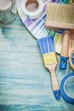 L'insieme delle latte della pittura spazzola il nastro adesivo del campionatore di colore su di legno Fotografia Stock