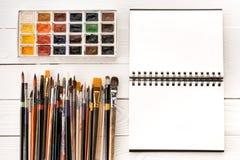 L'insieme delle pitture dell'acquerello, pennelli per la verniciatura ed apre il taccuino Fotografie Stock Libere da Diritti