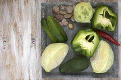 L'insieme delle verdure su bianco ha dipinto il piatto ed il fondo di legno: cavolo, cavolo rapa, cetriolo, pepe, avocado Fotografie Stock