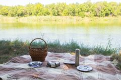 L'insieme di picnic, la coltelleria del metallo, termos, placca le tazze di tè plaid e tovagliolo marroni dal lago nei precedenti fotografie stock libere da diritti