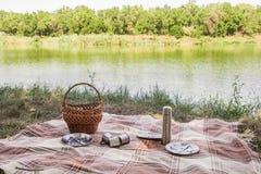 L'insieme di picnic, la coltelleria del metallo, termos, placca le tazze di tè plaid e tovagliolo marroni dal lago nei precedenti immagine stock