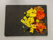 L'insieme di tre prosciutti spagnoli e un insieme dei formaggi francesi Fotografie Stock