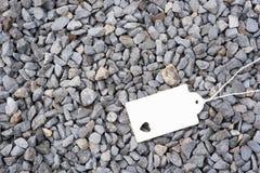 L'insigne blanc avec la forme de coeur se trouve sur des pierres Photo libre de droits