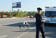 L'inspecteur de la police de la circulation entretient des moniteurs l'itinéraire utilisant le quadcopter images libres de droits