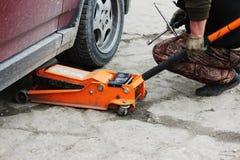l'installation de la roue de voiture de tourisme et le remplacement l'hiver fatiguent Photo libre de droits