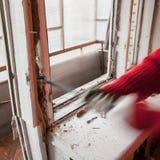 l'installatore che per mezzo del bastone a leva smantella il vecchio fram della finestra immagine stock