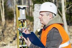 L'installatore delle telecomunicazioni vicino alla comunicazione cabla la recinzione Fotografia Stock