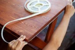 L'installazione ha condotto l'illuminazione di striscia per la tavola di legno di sotto fotografia stock
