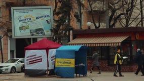 L'instigateur de rue distribue des journaux et des matériaux de campagne près des tentes annonçant le candidat pour le président  clips vidéos