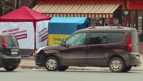 L'instigateur de rue distribue des journaux et des matériaux de campagne près des tentes annonçant le candidat pour le président  banque de vidéos
