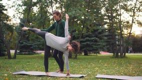 L'instructeur amical de yoga aide l'étudiante à maintenir la pose Ardha Chandrasana de demi-lune se tenant près de elle banque de vidéos