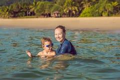 L'instructeur de natation de femme pour des enfants enseigne un garçon heureux à nager en mer photo libre de droits