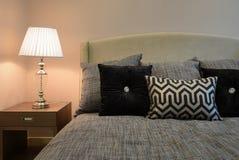 L'intérieur élégant de chambre à coucher avec le noir a modelé des oreillers sur le lit et la lampe de table décorative photos stock