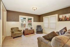 L'intérieur américain de salon avec les murs bruns et la planche blanche lambrissent l'équilibre photographie stock