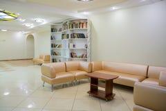 L'intérieur dans le lobby du théâtre pour de jeunes assistances Livres sur les étagères, meubles en cuir tapissés images libres de droits