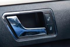 L'intérieur de la voiture avec vue sur le panneau de porte, la poignée et les boutons de serrure avec l'équilibre gris-clair image stock