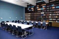 L'intérieur des couleurs de bibliothèque, bleues et brunes Bibliothèques avec des livres, tables blanches photo libre de droits