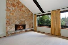 L'intérieur non meublé spacieux de salon avec le plafond voûté haut et la pierre équilibrent la cheminée photos libres de droits