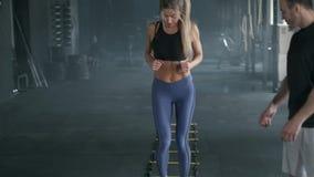 L'integrale giovane di una donna bionda sportiva sportiva e bella ? un cardio allenamento con un istruttore con le cinghie della  stock footage