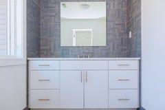 L'interior design contemporaneo del bagno piastrellato modello di pietra grigio con i dettagli di legno naturali minimi della mob immagine stock