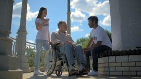 L'internazionale positiva si offre volontariamente la conversazione con un uomo wheelchaired archivi video